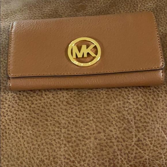 Coach wallet . A dark tan colour with gold MK